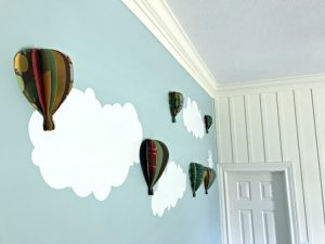 DIY paper hot air balloons on blue wall with white crown molding and board and batten.
