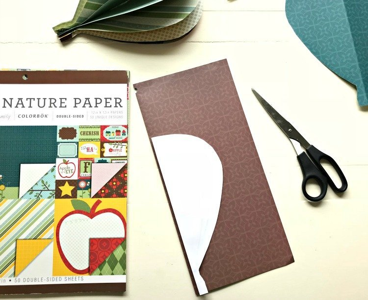A template for DIY Paper Hot Air Balloons folded in half on top of scrapbook paper.