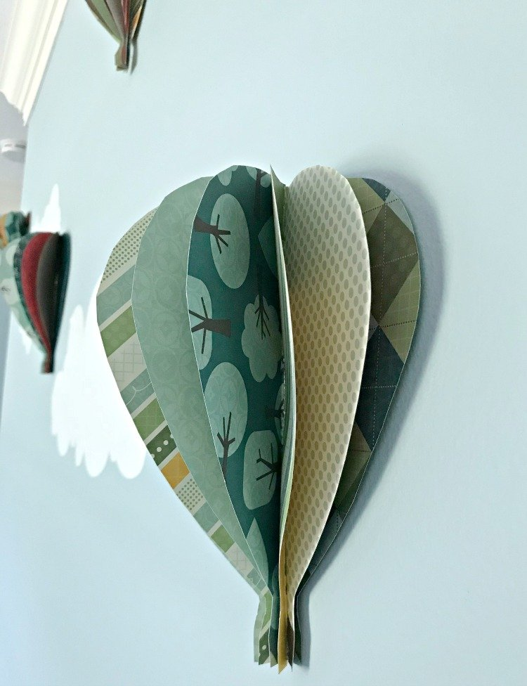 A close up look at a DIY Paper Hot Air Balloon hung on a blue wall.
