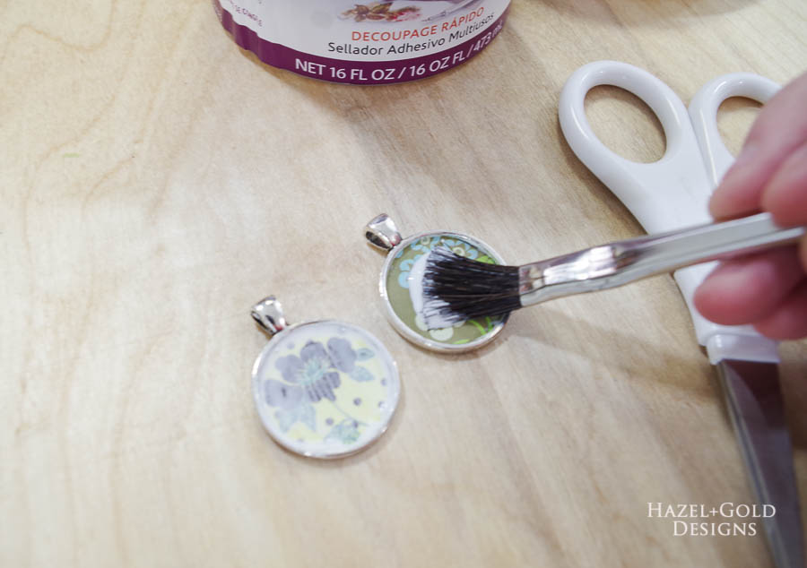 Place paper circles onto wet glue sealer - DIY Paper and Resin Pendant Necklace