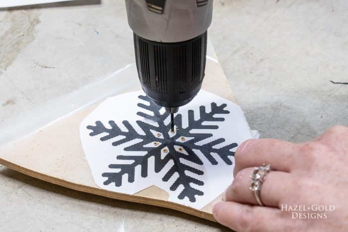 Use a drill to make a hole in the inner sections of each design