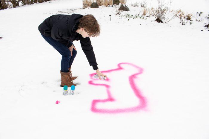 girl spraying unicorn design with shimmer spray chalk