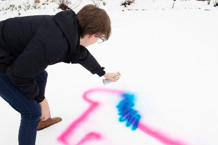 girl spraying unicorn in snow with testors shimmer spray chalk